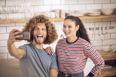 Playful couple taking a selfie in the kitchen at home - MCF00385