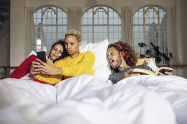 Happy friends having fun in bed at home with smartphone - MCF00388