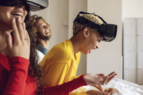 Happy friends having fun with VR glasses in bed at home - MCF00394