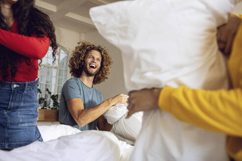 Happy friends having a pillow fight in bed at home - MCF00397