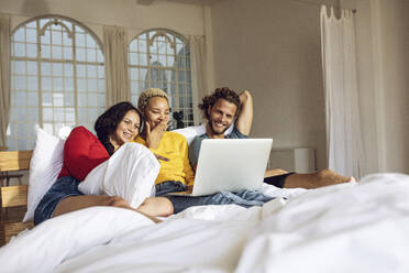 Happy friends relaxing in bed at home watching a movie on laptop - MCF00400