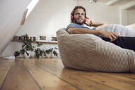 Young man relaxing in beanbag at home listening to music - MCF00403