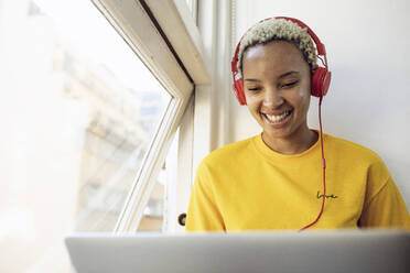 Happy young woman sitting at the window at home with laptop and headphones - MCF00409