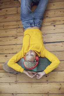 Young woman lying on skateboard on the floor at home listening to music - MCF00412