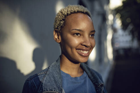 Portrait of smiling young woman in the city - MCF00415