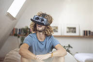 Young man wearing VR glasses at home - MCF00418