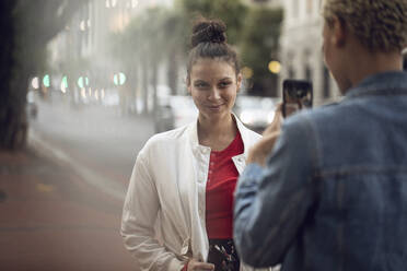 Young woman posing for a smartphone picture in the city - MCF00430