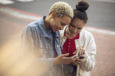 Two young women checking smartphone in the city - MCF00433