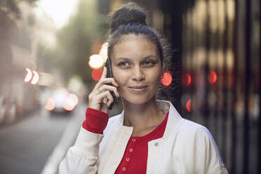 Portrait of young woman on the phone in the city - MCF00436