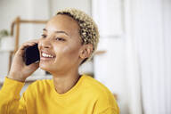 Portrait of happy young woman on the phone at home - MCF00439
