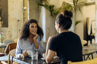 two girlfriends meeting and talking in a bistro - SODF00415