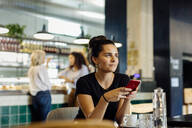 Young woman sitting in bistro, using smartphone - SODF00421