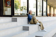 Mature businesswoman sitting on steps in the city, using smartphone - SODF00424