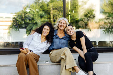 Three women sitting on bench inthe city, with arms around - SODF00430
