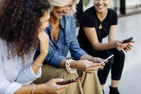 Three women sitting on steps in a row, using smartphones - SODF00433