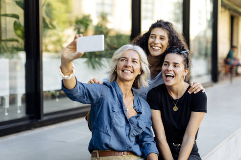 Three laughing women taking selfie in the city - SODF00436