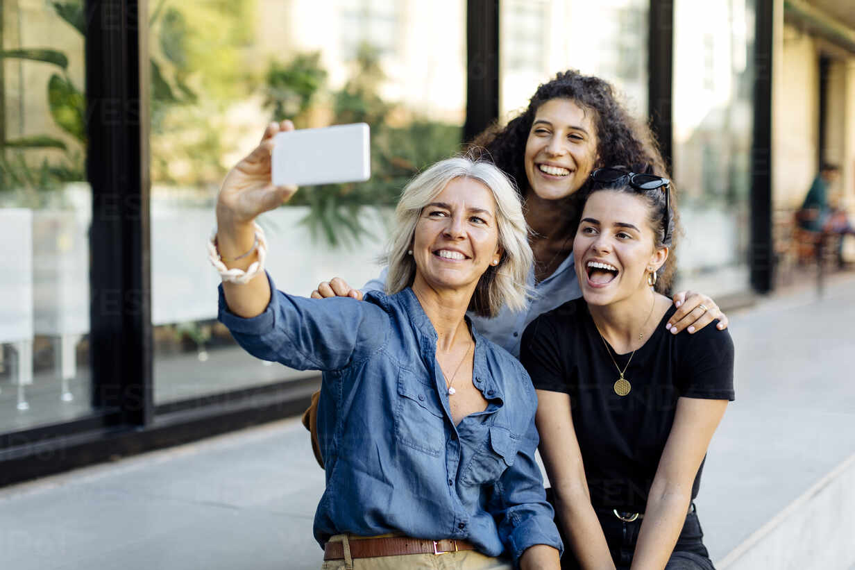 Three laughing women taking selfie in the city - SODF00436 - Sofie Delauw/Westend61