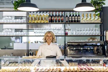 Proud bistro woner standing behind pastry counter - SODF00439
