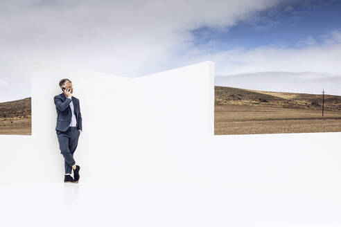 Businessman standing in empty space, talking on the phone - MCF00447