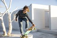 Girl skateboarding in front of white house - MCF00450