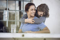 Girl embracing mother, sitting at home - MCF00456
