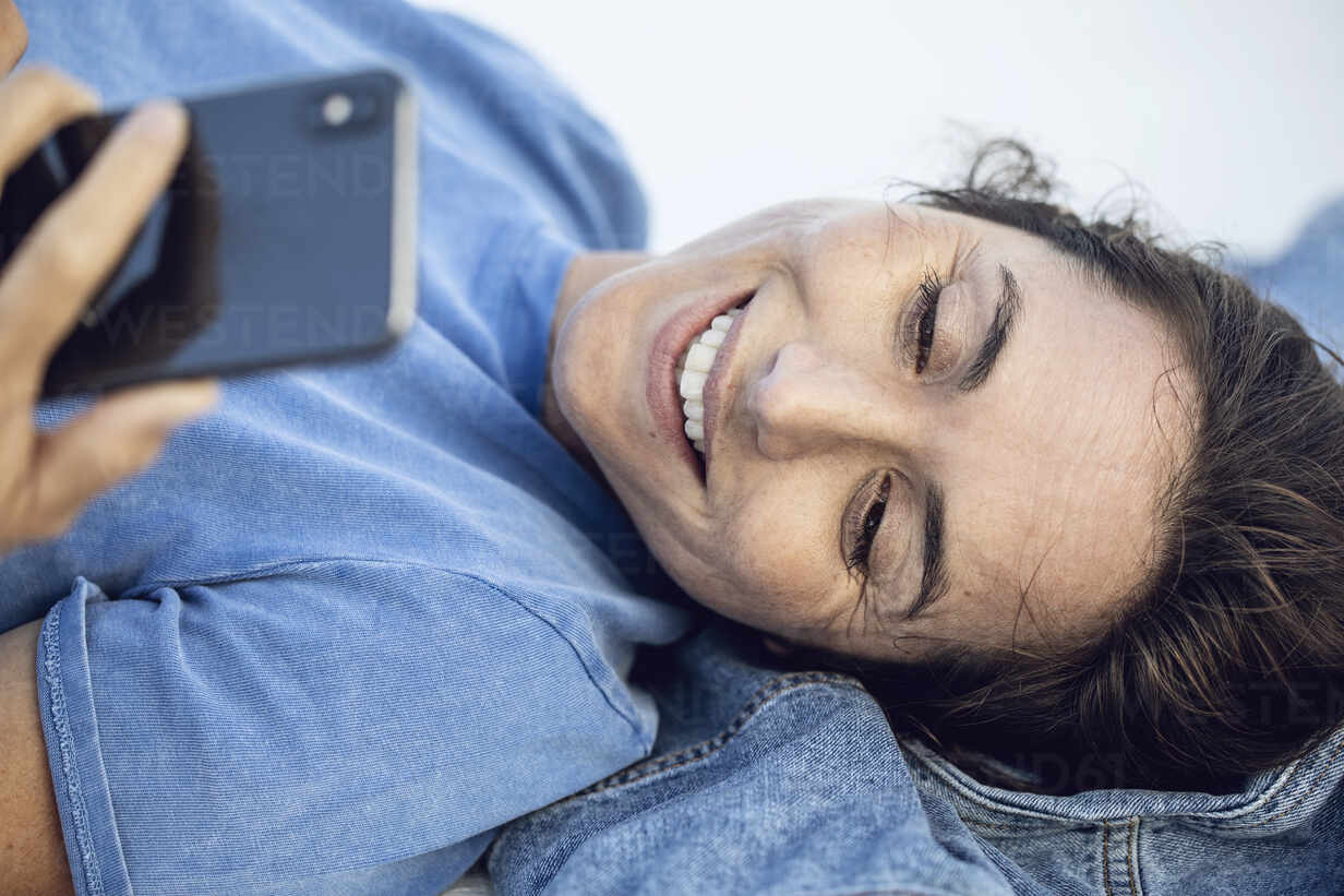 Young businesswoman relaxing, lying on wall, using smartphone - MCF00462 - Maya Claussen/Westend61