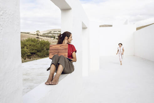 Mother using laptop with wooden cover, watching daughter running in white architecture - MCF00468