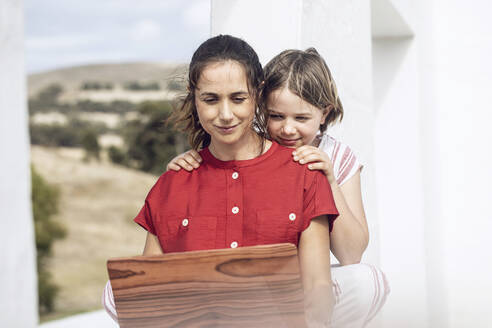 Girl watching mother using laptop with wooden cover - MCF00471