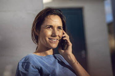 Portrait of a pretty, dark-haired woman, talking on the phone - MCF00474