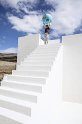 Little girl on white stairs, carrying inflatable globe - MCF00486