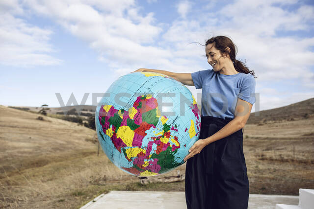 Mature woman holding inflatable globe, looking confident - MCF00489 - Maya Claussen/Westend61