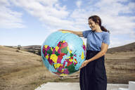 Mature woman holding inflatable globe, looking confident - MCF00489