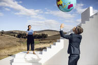 Businessman and woman playing with inflatable globe - MCF00492