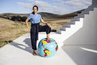 Confident woman putting foot on inflatable globe - MCF00495