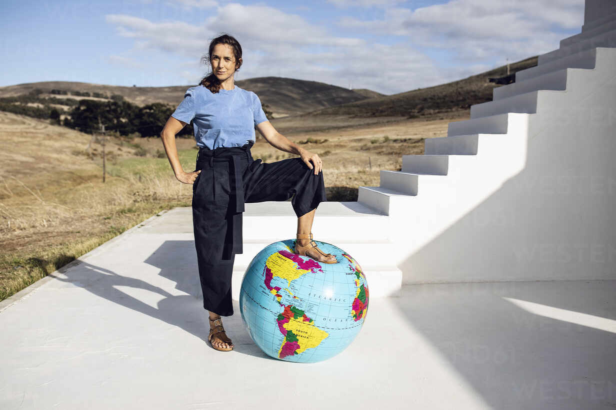 Confident woman putting foot on inflatable globe - MCF00495 - Maya Claussen/Westend61