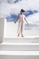 Girl standing on top of stairs, looking through VR goggles - MCF00507