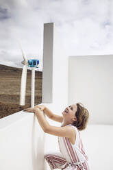 Girl looking at small wind turbine on white wall - MCF00510