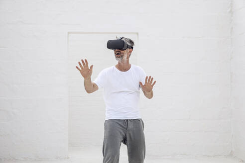 Mature man discovering empty space with VR goggles - MCF00519