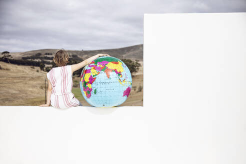Little girl sitting on wall, with arm aroung inflatable globe, rear view - MCF00522