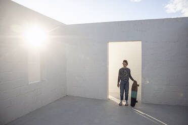 Girl with skateboard standing in empty, sunlit space - MCF00528