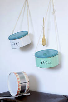 Toy drums made from cookie jars hanging on wall - GISF00481