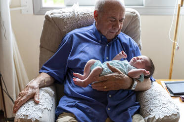 Grandfather sitting in an armchair holding a newborn baby - GEMF03309