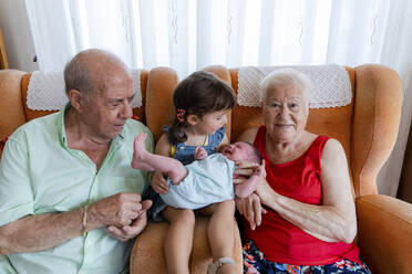 Grandparents with little girl and newborn baby at home - GEMF03312