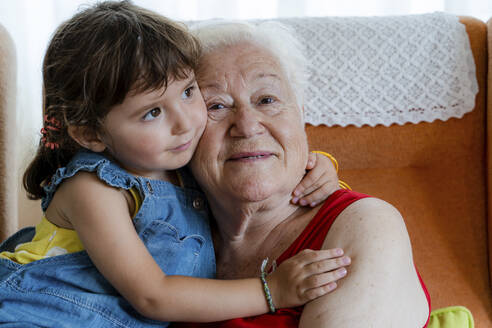 Smiling grandmother hugging her granddaughter at home - GEMF03315