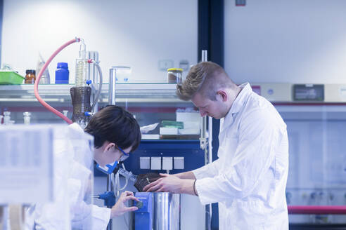 Female and male laboratory technician working together in a laboratory - SGF02453