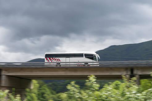 Spain, Elgoibar, Bus on elevated road in landscape - MTBF00248