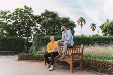 Gay couple relaxing with coffee to go on wooden bench in a park, Barcelona, Spain - AFVF04323