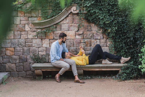 Gay couple relaxing together on a bench - AFVF04326