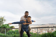 Portrait of happy gay couple having fun on view terrace, Barcelona, Spain - AFVF04344