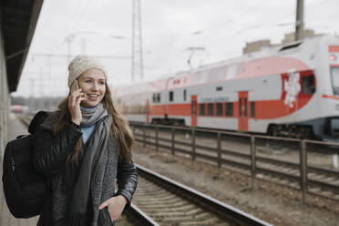 Portrait of smiling young woman on the phone waiting on platform, Vilnius, Lithuania - AHSF01594